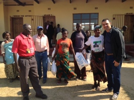 Dennis handing out a bag of mealie meal (a staple food item in the Zambian diet) to parents at the end of Term 2.